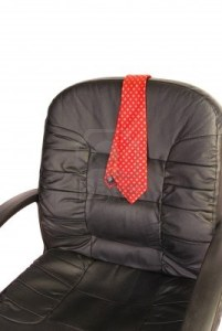 1481330-red-mens-neck-tie-draped-over-the-back-of-a-black-office-desk-chair-iso